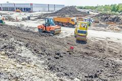 Landscape transform into urban area with machinery, people are working. Stock Photos
