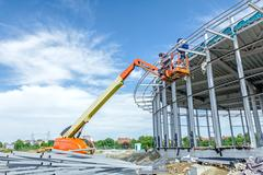 Height workers with help of cherry picker are working on new metal canopies Stock Photos