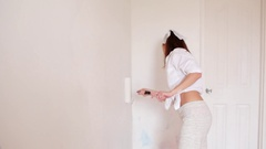 The young woman is painting the room in white color and smiling Stock Footage