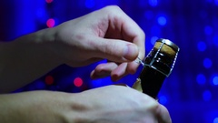 The man opens a bottle of champagne close-up. In the background, bokeh lights Stock Footage