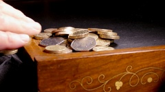 Man's hand sliding sterling coins from a desk into a bag. Stock Footage
