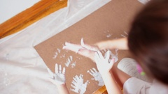 A little cute happy funny child painting white handprints with mother together Stock Footage