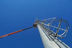 Hydraulic mobile construction platform elevated towards a blue sky with metal Stock Photos