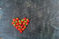 Fresh strawberries array heart shape on old wooden background Stock Photos