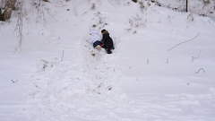 Children are trying to ride on the hillside. Boy and girl roll down the hill Stock Footage