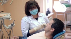 Female dentist making procedures to male patient at clinic, close up Stock Footage