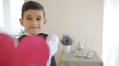 A very happy smiling boy is showing a red heart. valentines day, Stock Footage