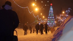 Lights on the Christmas tree. Christmas decoration, people walking outdoors Stock Footage