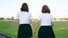 Two Asian Thai college student girl in university uniform holding hands playing Stock Footage