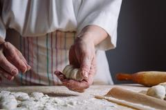 Two hands making dough for meat dumplings. Stock Photos