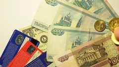 Drop gold coins on banknotes Russian rubles US dollars and plastic credit cards Stock Footage