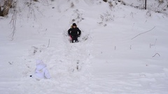 Children are trying to ride on the hillside. Boy and girl roll down the hill. Stock Footage