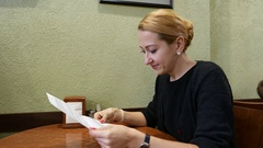 Woman read paper letter at cafe, side portrait shot Stock Footage