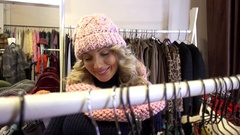 Beautiful Blonde young Woman shopping in a Clothing Store in a Mall Stock Footage