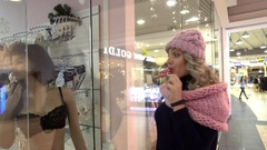 Beautiful Blonde young Woman shopping Mall considers mannequins in shop window Stock Footage