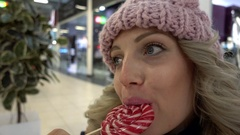 Beautiful Blonde young Woman licking Lollipop during the Christmas Fair in Mall Stock Footage