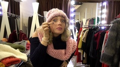 Beautiful Blonde young Woman shopping in a Clothing Store in a Mall looks Mirror Stock Footage