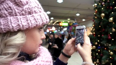 Woman Blonde taking Photo with Mobile Phone on Christmas Fair Tree in Mall Stock Footage