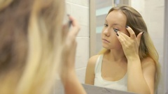 Beautiful young woman is doing makeup in front of the mirror. Stock Footage