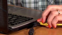 Female hand disconnect usb, vga and lan cables from laptop on table Stock Footage