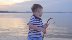 Caucasian boy in a striped vest on the waterfront. Joyful in the background Stock Footage