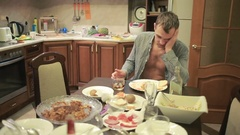 Young man with a hangover at the table in the kitchen. after party Stock Footage