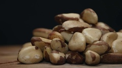 Pile of brazil nuts on a wooden table isolated on black Stock Footage
