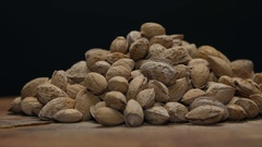 Pile of almonds in shell on a wooden table isolated on black Stock Footage