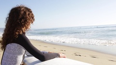 A young woman surfer sitting on beach holding surfboard as she looks out towards Stock Footage