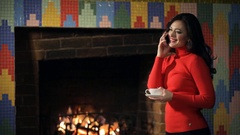 Beautiful woman stands by the fireplace and talking on the phone Stock Footage