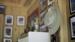 A older hiker grabbing hat from inside a cabin in the woods. Stock Footage
