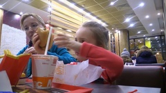 Little girl and mom eating hamburger, fries and drink cola in eatery fastfood Stock Footage