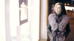 Winter dressed young woman comes up to the window display of expensive boutique Stock Footage