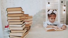 Schoolgirl sitting at a table and reading a book Stock Footage