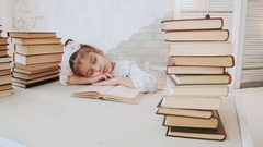 Little girl in school uniform, fell asleep while reading a book Stock Footage