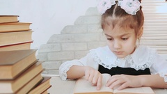A child sitting at the table leads finger across the page book in the foreground Stock Footage