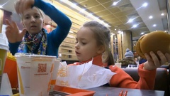 Girl and mom eating hamburger, fries potato and drink cola in eatery fastfood Stock Footage