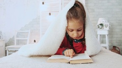 Portrait of cute school girl reading a book in pajamas, covered with white Stock Footage
