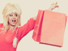 Woman wearing furry hat holding shopping bags Stock Photos