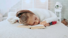 Little girl in pajamas, fell asleep while reading a book, covered with white Stock Footage