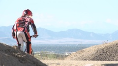 A young woman bmx rider riding on dirt track, super slow motion. Stock Footage