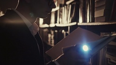 A young man with a flashlight at night looking documents in libraries Stock Footage
