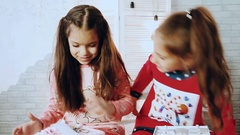 Little kids in pajamas sitting, and they give each other gifts Stock Footage