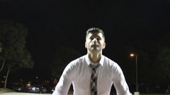 A young business man shooting free throws on an outdoor basketball court at nigh Stock Footage