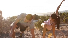 A young man and woman couple stretching together before going trail running. Stock Footage