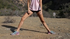 A young woman runner stretching before going on a trail run. Stock Footage