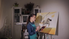 The artist paints a picture. Girl artist mixes paint brush on the palette Stock Footage