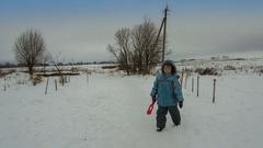 Cute little boy walking on snow road in the village Stock Footage