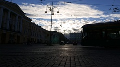 Dark square at evening, bright white clouds on sky, tram turn, two bicycle ride Stock Footage