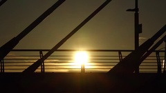 Tram car pass on bridge against setting sun, black silhouetted view Stock Footage